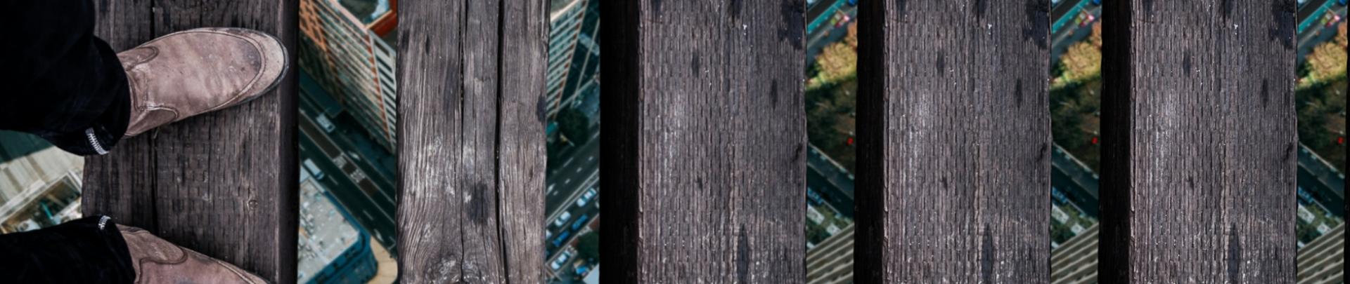 Een man staat op een houten brug zwevend boven flats